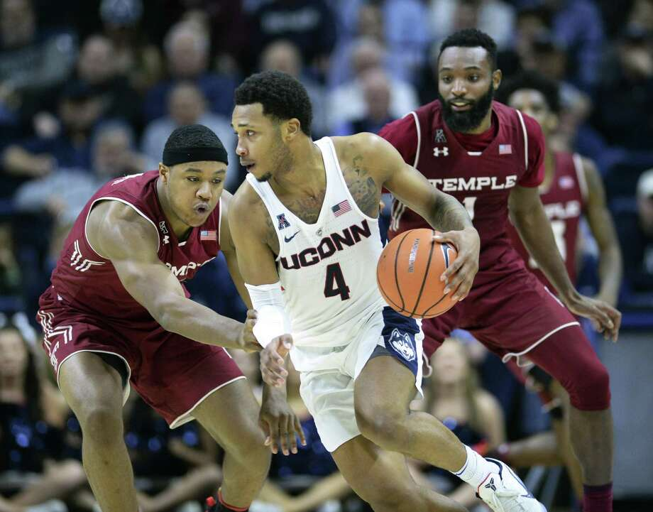 UConn's Jalen Adams (4) dribbles around Temple's J.P. Moorman II (4) and Josh Brown (1) in the second half of on Feb. 28 in Storrs. Photo: Stephen Dunn / Associated Press / FR171426 AP