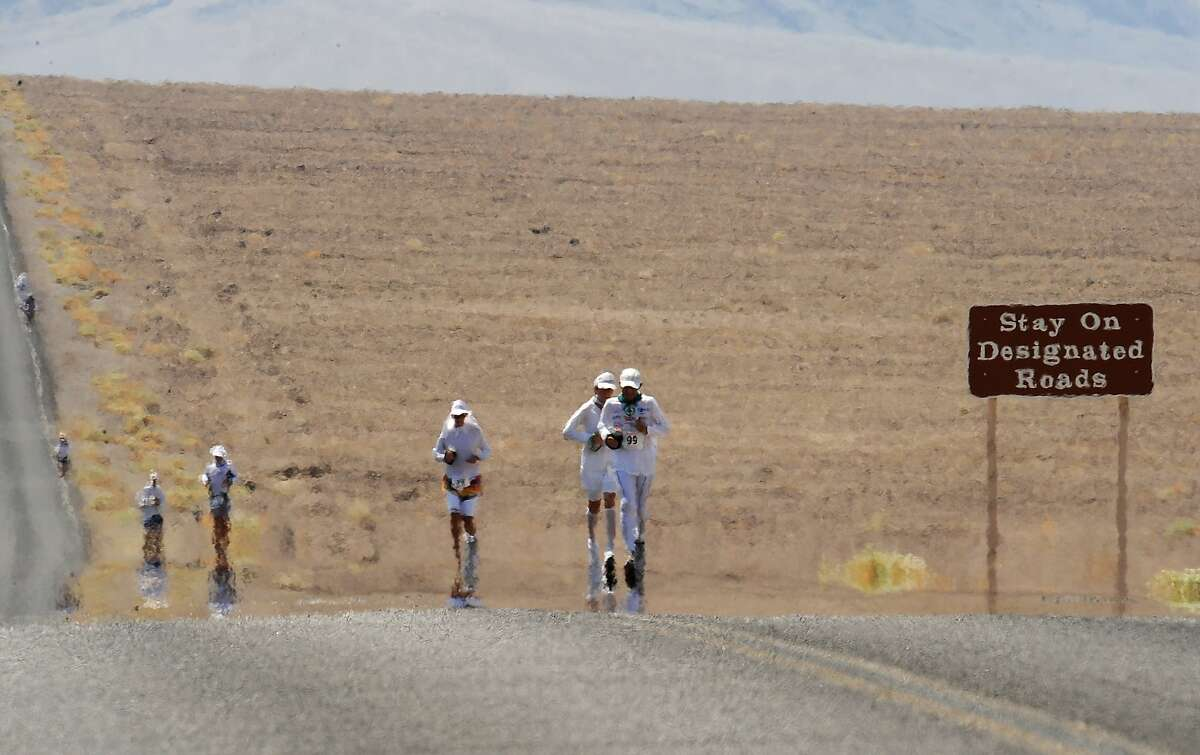Competitors appear to shimmer as they run on the 145F pavement, in the 2008 Badwater Ultramarathon, in Death Valley, California on July 14, 2008. With air temperatures reaching as high as 130F (55C), the 135 miles (217 km) course crosses desert as low as 280 feet (85 m) below sea level at Badwater on the way to the Mt. Witney Portal at 8,360 feet (2533m). The winner normally crosses the finish line in less than 24 hours, while the course stays open for 60 hours. AFP PHOTO / Robyn Beck / AFP PHOTO / ROBYN BECK (Photo credit should read ROBYN BECK/AFP/Getty Images)