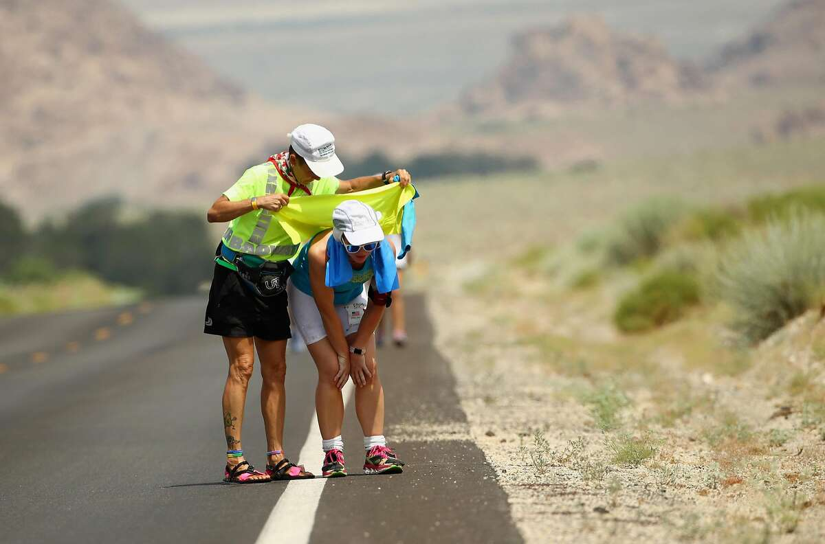 DEATH VALLEY, CA - JULY 12: Collen Zato is looked after by a member of her support crew during the STYR Labs Badwater 135 on July 12, 2017 in Death Valley, California. The start of the 135 mile race is at Badwater Basin, Death Valley, which marks the lowest elevation in North America at 280 feet below sea level. The race finishes at Whitney Portal at 8,360 feet. The course covers three mountain ranges for a total of 14,600 feet of cumulative vertical ascent. Whitney Portal is the trailhead to the Mt. Whitney summit, the highest point in the contiguous United States. The hottest temperature in the world was recorded in Death Valley with a temperature of 134 degrees (56.6 Celcius). (Photo by Ezra Shaw/Getty Images)