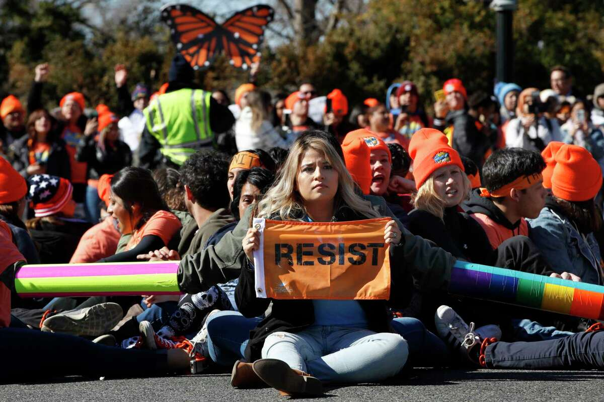"""A woman holds up a sign that says, """"resist,"""" as supporters of the Deferred Action for Childhood Arrivals (DACA) block an intersection near the U.S. Capitol as an act of civil disobedience in support of DACA recipients, Monday, March 5, 2018, on Capitol Hill in Washington."""