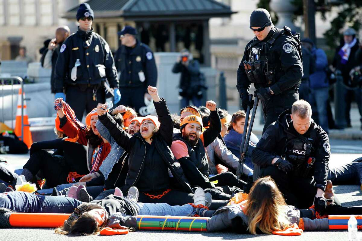 U.S. Capitol Police use bolt cutters to break chains locking together supporters of the Deferred Action for Childhood Arrivals (DACA) program, as the protesters cheer in support of DACA, Monday, March 5, 2018, on Capitol Hill in Washington. The protesters were participating in an act of civil disobedience after a march in support of DACA.