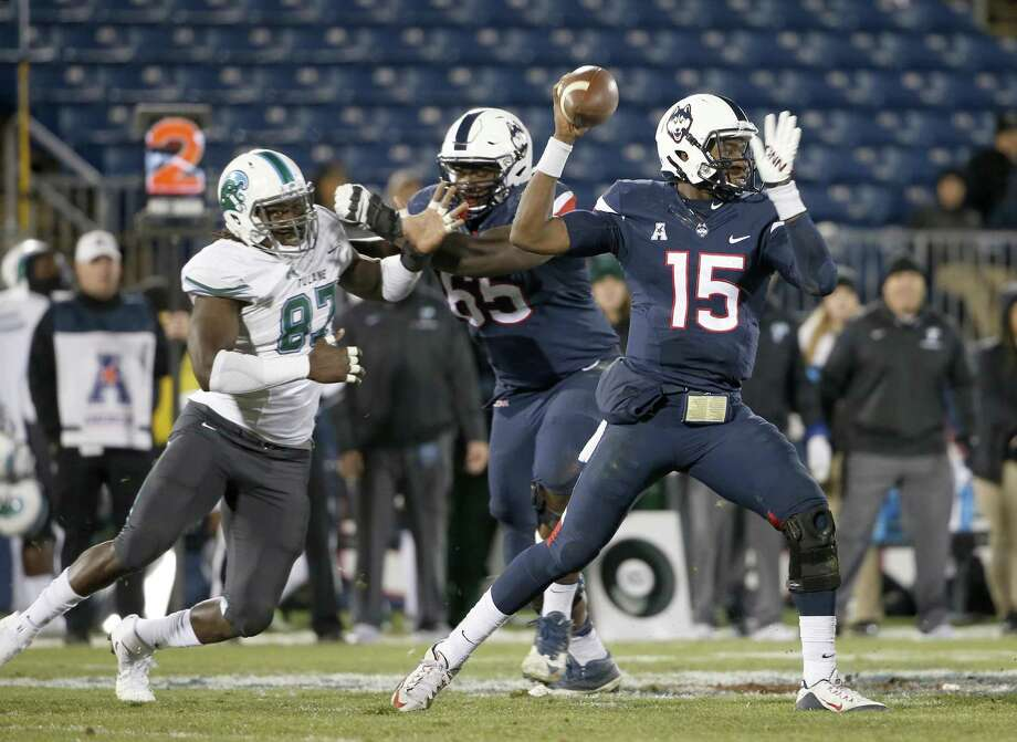 Connecticut quarterback Donovan Williams (15) passes under pressure as he gets a block from offensive lineman Matt Peart (65) on Tulane defensive end Ade Aruna (87) during the second half of a game in East Hartford, Nov. 26, 2016. Peart will be making a move from left to right tackle. Photo: Mary Schwalm / Associated Press / FR158029 AP