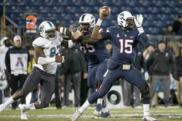 Connecticut quarterback Donovan Williams (15) passes under pressure as he gets a block from offensive lineman Matt Peart (65) on Tulane defensive end Ade Aruna (87) during the second half of a game in East Hartford, Nov. 26, 2016. Peart will be making a move from left to right tackle.