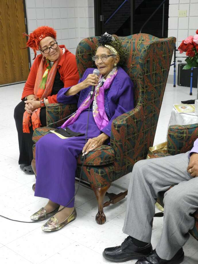 Sitting next to her daughter Sandra Franklin, Essie Givens takes the microphone to reminisce during her 100thbirthday celebration. Photo: Gail M. Williams