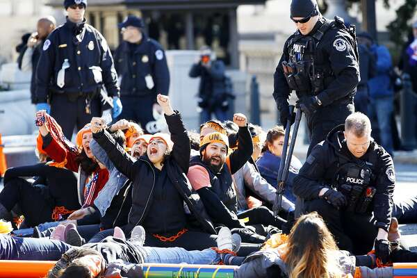 U.S. Capitol Police use bolt cutters to break chains locking together supporters of the Deferred Action for Childhood Arrivals (DACA) program, as the protesters cheer in support of DACA, Monday, March 5, 2018, on Capitol Hill in Washington. The protesters were participating in an act of civil disobedience after a march in support of DACA. (AP Photo/Jacquelyn Martin)