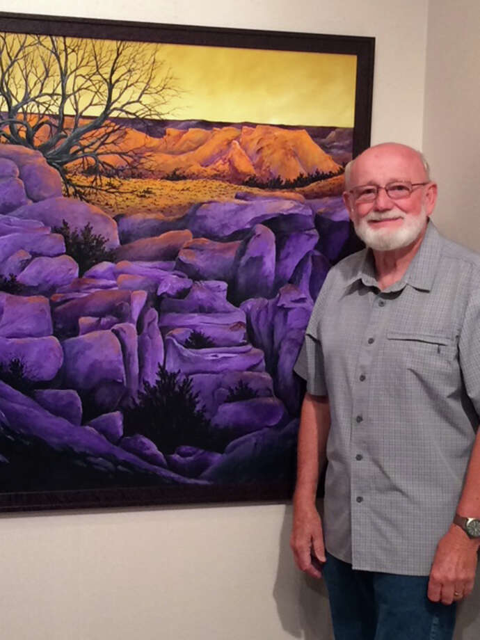 Teacher and artist Jon Birdsong stands next to a recent painting.