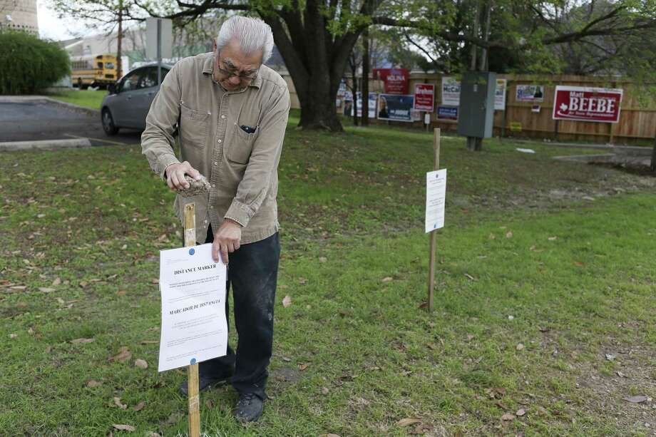 Ruben Villagran sets up distance markers at the Brook Hollow Library  polling site, Monday, March 5, 2018. The Bexar County Elections Department distributed voting machines on Saturday for TuesdayÕs primary election. Photo: JERRY LARA / San Antonio Express-News / © 2018 San Antonio Express-News
