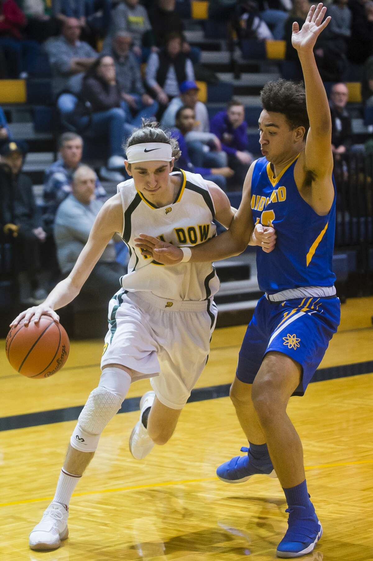 Dow senior Zac Chichester dribbles toward the basket while Midland junior Isaiah Bridges guards him during their district quarterfinals game on Monday, March 5, 2018 at Mt. Pleasant High School. Dow won 54-40 and will advance to play Mt. Pleasant on Wednesday. (Katy Kildee/kkildee@mdn.net)