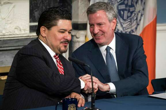 In this photo provided by the Mayoral Photography Office, Richard A. Carranza, left, is introduced by New York Mayor Bill de Blasio, right, as his new choice to lead the nation's largest school system Monday, March 5, 2018, at City Hall in New York. Carranza, who has been the superintendent in Houston since August 2016 and previously was superintendent of the San Francisco school system, has been appointed to replace Chancellor Carmen Farina, who's retiring. (Ed Reed/Mayoral Photography Office via AP)