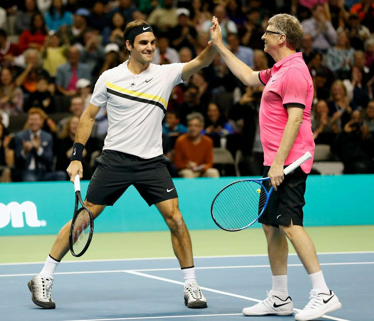 Roger Federer and Bill Gates high five while defeating Jack Sock and Savannah Guthrie during the pro/celebrity doubles tennis match during The Match for Africa at the SAP Center in San Jose, Calif., on Monday, March 5, 2018.