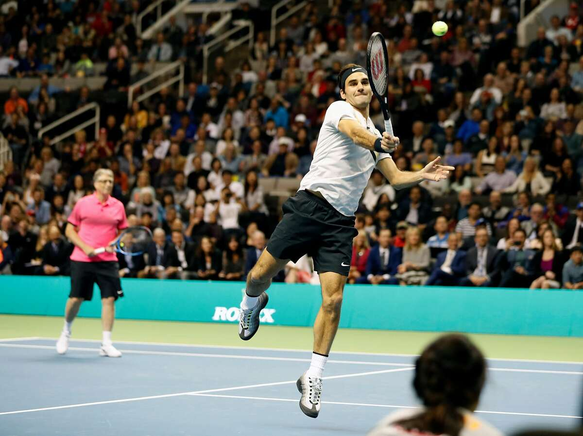 Roger Federer hits a forehand as he and Bill Gates team up to defeat Jack Sock and Savannah Guthrie during the pro/celebrity doubles tennis match during The Match for Africa at the SAP Center in San Jose, Calif., on Monday, March 5, 2018.
