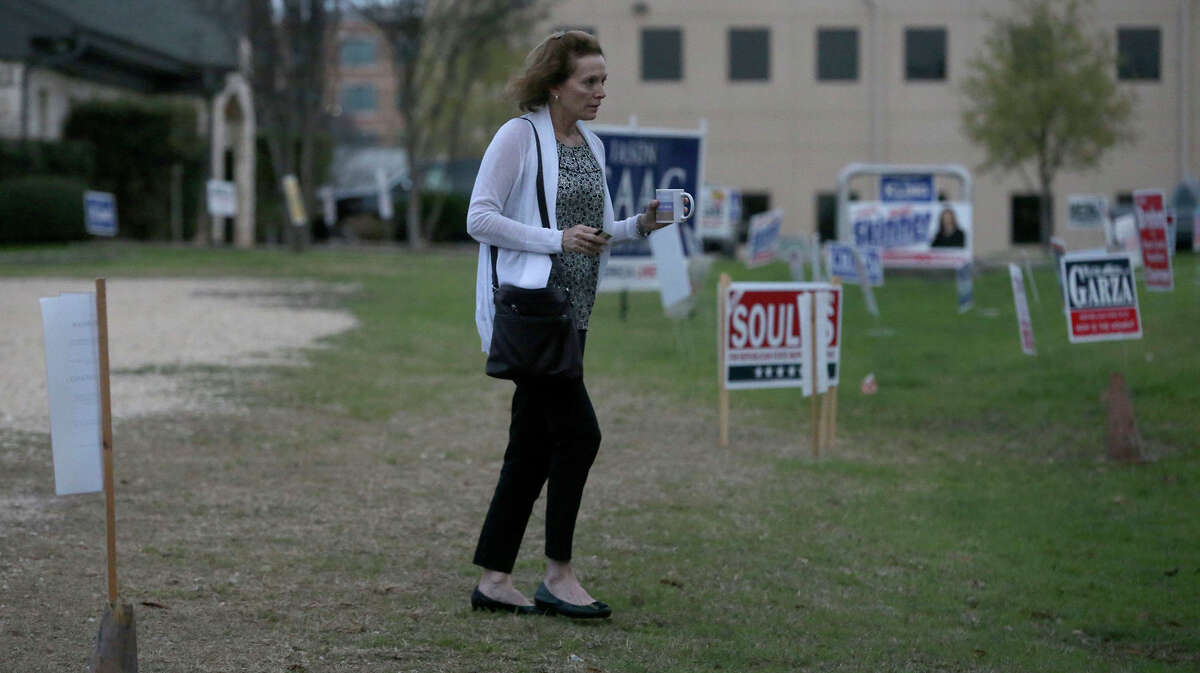 A woman with a coffee cup in hand heads to the polls at the Brook Hollow Branch of the San Antonio Public Library Tuesday March 6, 2018. Polls open today for party primaries as voters decide on a mix of races.