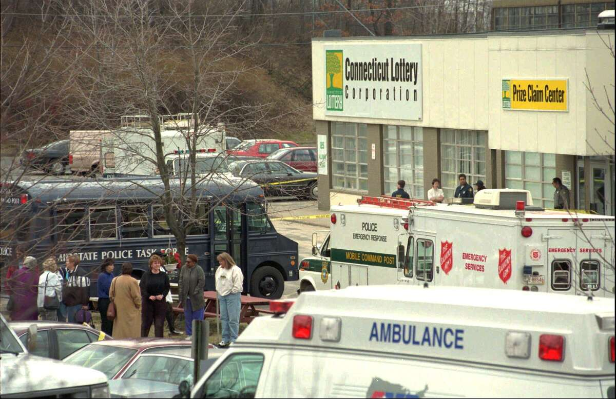 People and emergency vehicles gather outside the Connecticut State Lottery headquarters in Newington on March 6, 1998, after four people, including lottery head Otho Brown, were shot to death by another employee.