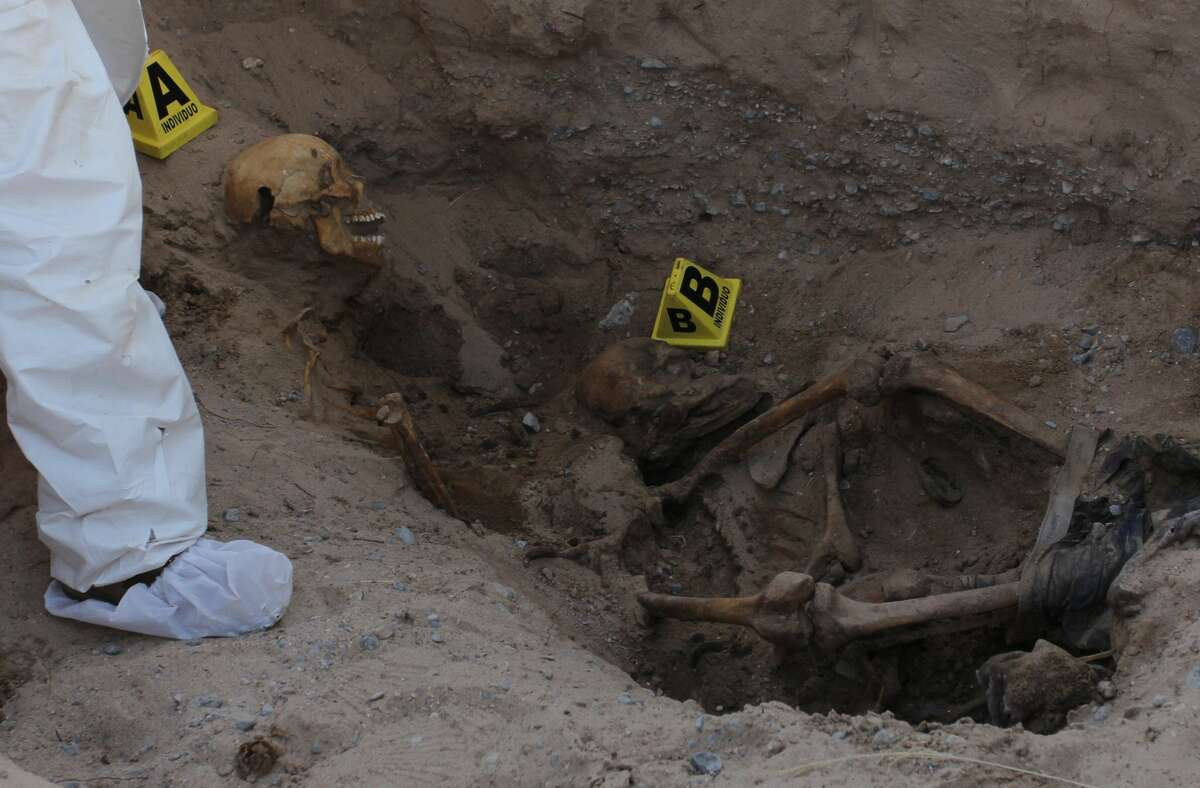 Experts from the Chihuahua state Prosecutor's Office work in a clandestine grave where the remains of two people were found in the desert of the Juarez Valley, in Ciudad Juarez, Chihuahua state, Mexico on March 2, 2018. According to official figures from the State Attorney's Office, some 138 bones have been found from 2017 to today's date. / AFP PHOTO / HERIKA MARTINEZ (Photo credit should read HERIKA MARTINEZ/AFP/Getty Images)