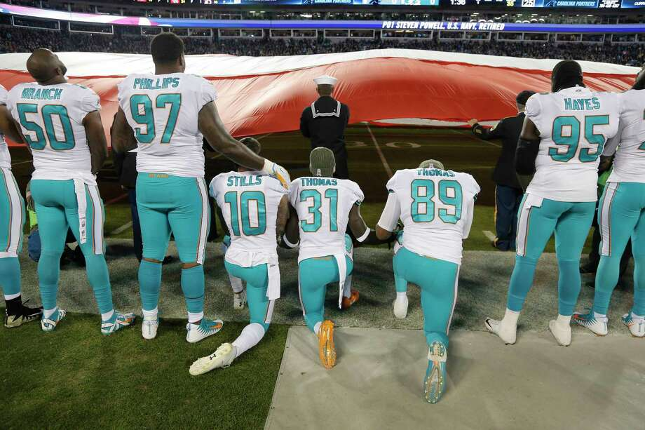 Miami Dolphins players participate in the national anthem before an NFL football game between the Carolina Panthers and the Miami Dolphins in Charlotte, N.C., Monday, Nov. 13, 2017. (AP Photo/Bob Leverone) Photo: Bob Leverone, Associated Press / FR170480 AP