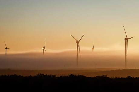 A thick cloud of fog and morning light engulfs several 285ft tall 2.5 MW Clipper wind turbines at the BP Sherbino Mesa II Wind Farm, Monday, Feb. 20, 2012, in Fort Stockton.