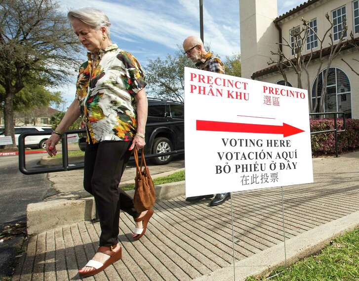 Voters walk out of the primary election polling place at St. Anne's Catholic Church on Tuesday, March 6, 2018, in Houston.