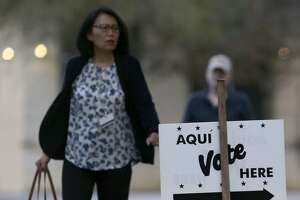 A woman with purse in hand heads to the polls at the Brook Hollow Branch of the San Antonio Public Library Tuesday March 6, 2018. Polls open today for party primaries as voters decide on a mix of races.