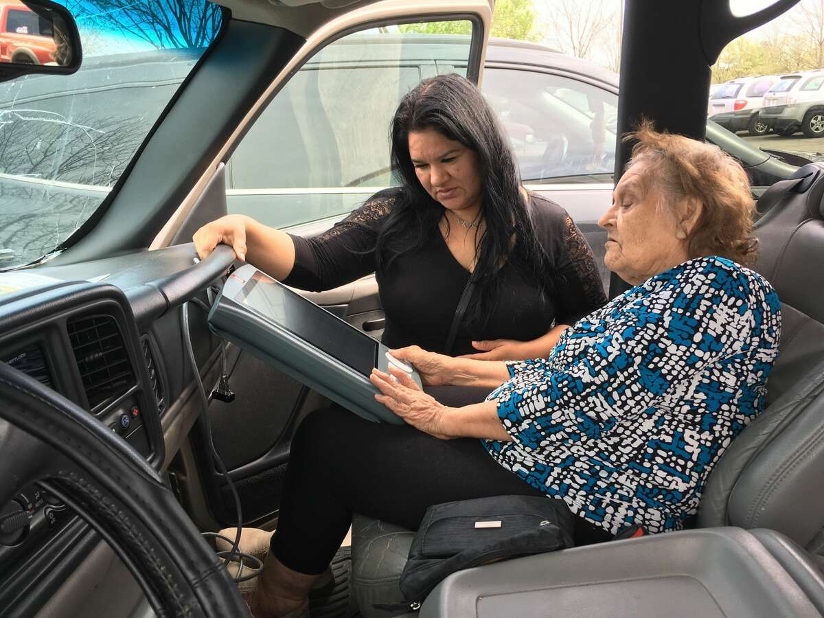 Maria Escovedo, 80, of the East End, votes in her daughter's car with help from her daughter, at Ripley Neighborhood Centers Inc. on March 6, 2018.