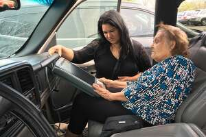 Maria Escovedo, 80, of the East End, votes from her daughter's car with help from election judge Jael Casiano, at Ripley Neighborhood Centers Inc. on March 6, 2018.