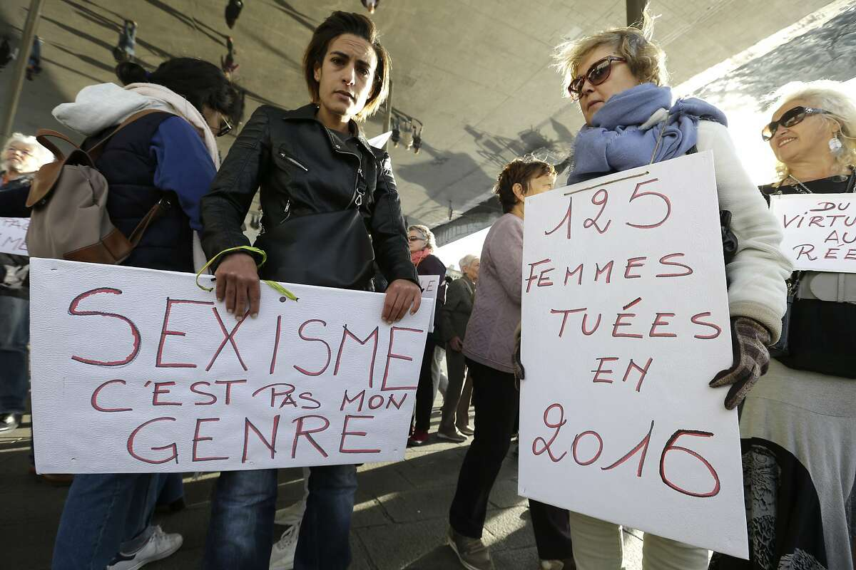 """FILE - In this Oct. 29, 2017 file photo, demonstrators hold placards reading """"Sexism, that is not my gender"""" and """"125 women killed in 2016"""", right, during a demonstration against sexual abuse and harassment across the country under the #MeToo movement, in Marseille, southern France. Perhaps no country has had more complex reaction to #MeToo than France - long identified as a haven for romance. The government is preparing new legislation on sexual violence and harassment, and some lawmakers want to impose fines for sexist catcalls. Yet despite sexual misconduct allegations against several prominent men, they haven't lost their jobs or reputations. Meanwhile, French feminists ranks have experienced divisions. (AP Photo/Claude Paris, File)"""
