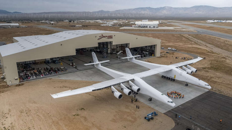 FILE-- Paul Allen's Stratolaunch airplane emerges from its hangar in Mojave, California on May 31, 2017. Stratolaunch provided the first details about a new family of launch vehicles it has in the works, including two types of rockets and a reusable space plane that could someday carry astronauts to orbit. Photo: Photo Courtesy Of Stratolaunch Systems Corp. / Photo courtesy of Stratolaunch Systems Corp.
