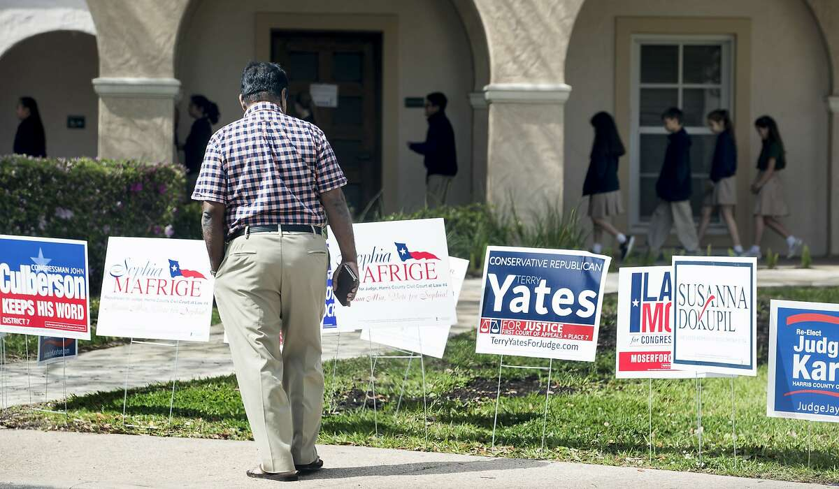 A voter stops to look at primary election signs outside the polling place at St. Anne's Catholic Church on Tuesday, March 6, 2018, in Houston. ( Brett Coomer / Houston Chronicle )