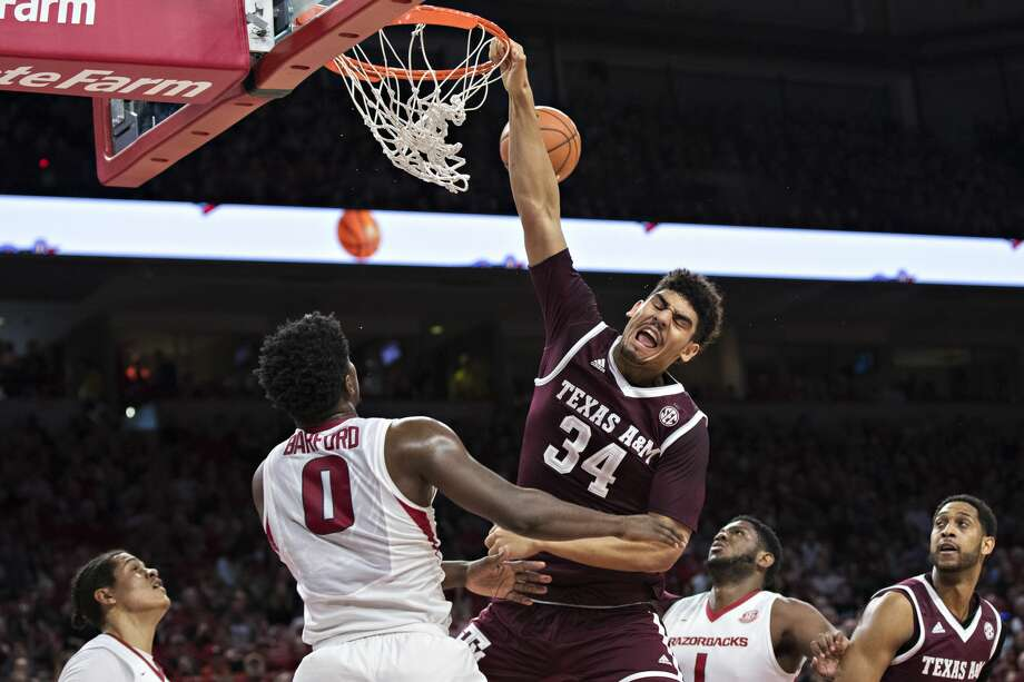 FAYETTEVILLE, AR - FEBRUARY 17:  Tyler Davis #34 of the Texas A&M Aggies goes up for a dunk and is fouled by Jaylen Barford #0 of the Arkansas Razorbacks at Bud Walton Arena on February 17, 2018 in Fayetteville, Arkansas.  The Razorbacks defeated the Aggies 94-75.  (Photo by Wesley Hitt/Getty Images) Photo: Wesley Hitt/Getty Images