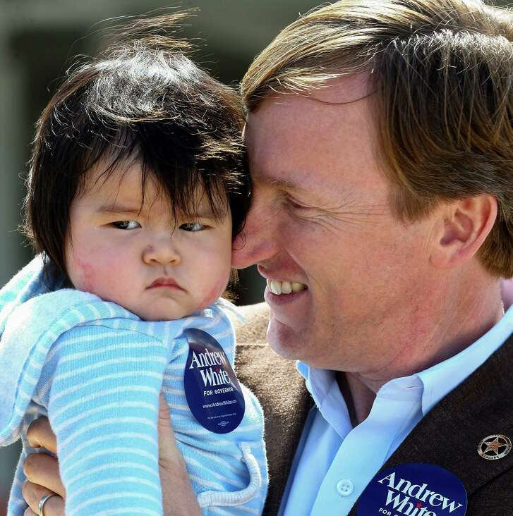 Gubernatorial candidate Andrew White, right, holds six-month-old Max while talking to Max's father Peter Kim outside the West Gray Recreation Center  Tuesday, March 6, 2018, in Houston.