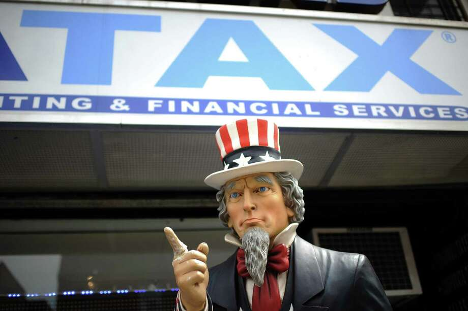 A tall statue representing Uncle Sam stands outside a tax preparation office in Queens, N.Y. A loophole that allows high earners to reduce their taxes lies in the law's 20 percent deduction for owners of small businesses run as partnerships, limited liability companies and the like. These so-called pass-through entities underpin the U.S. economy, ranging from small-town builders to law practices, but also private-equity and hedge fund firms. Photo: Anthony Behar /TNS / Sipa USA