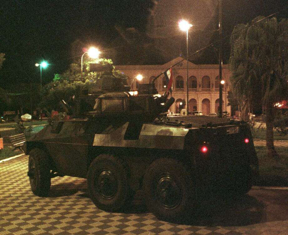 An armoured personel carrier driven by rebel soldiers heads toward the Congress, in Asuncion, the Paraguayan capital in 2001 during a coup attempt. The critical lesson in South America for the U.S. is that once democracy and rule of law are broken, they are hard to fix. Photo: DANIEL GOMEZ /AP / AP