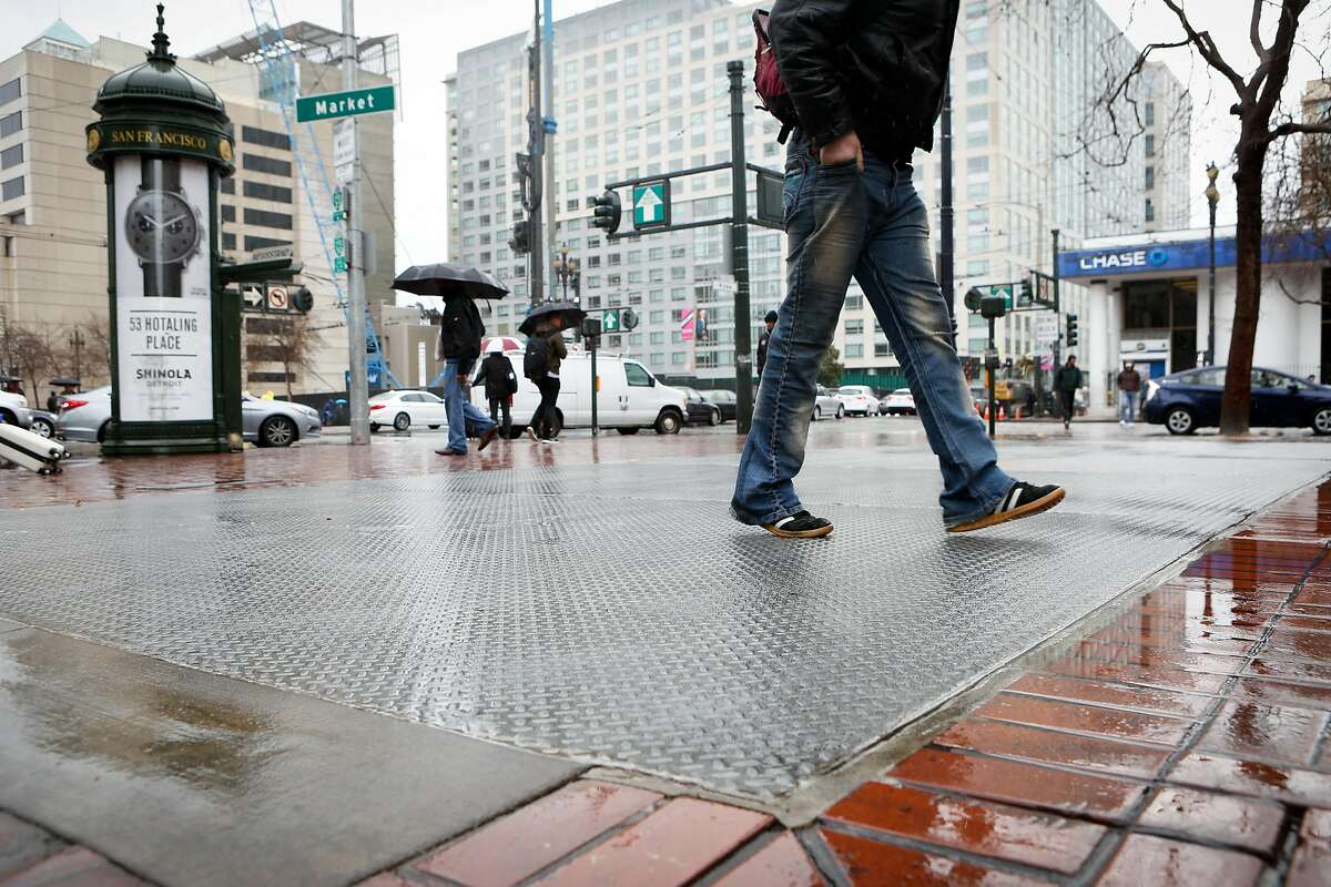 Pedestrians walk over a metal grate that covers a closed entrance for Civic Center Station on Thursday, February 28, 2018 in San Francisco, California.