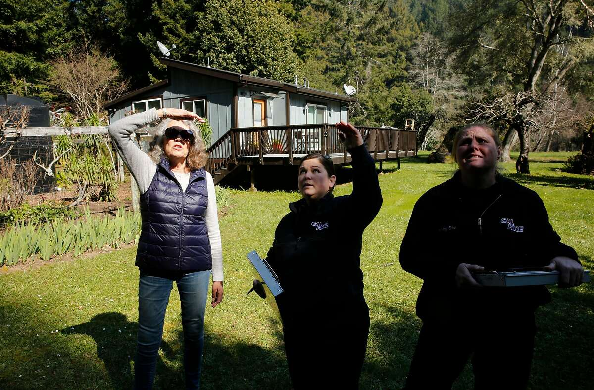 (l to r) Cal Fire inspectors Kara Eggert, (center) and Jenny shu, (right) conduct a defensible space inspection at the home of Marsha Skinner, (left) in rural western Sonoma County, Calif., on Tues. Feb. 27, 2018.