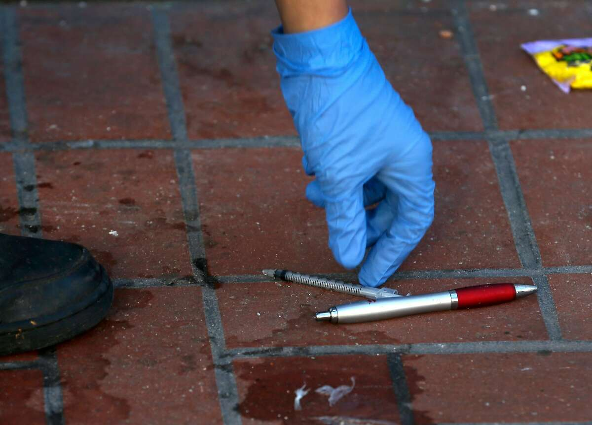 Michael Lopez, with the Central Market Community Benefit District, picks up a needle and other debris lying on the sidewalk on Market Street near Seventh Street in San Francisco, Calif. on Tuesday, March 6, 2018.