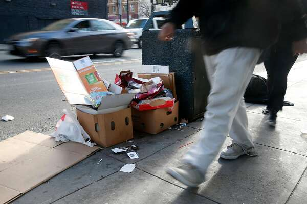 Pedestrians walk past trash left next to a waste bin at Seventh and Market streets in San Francisco, Calif. on Tuesday, March 6, 2018.