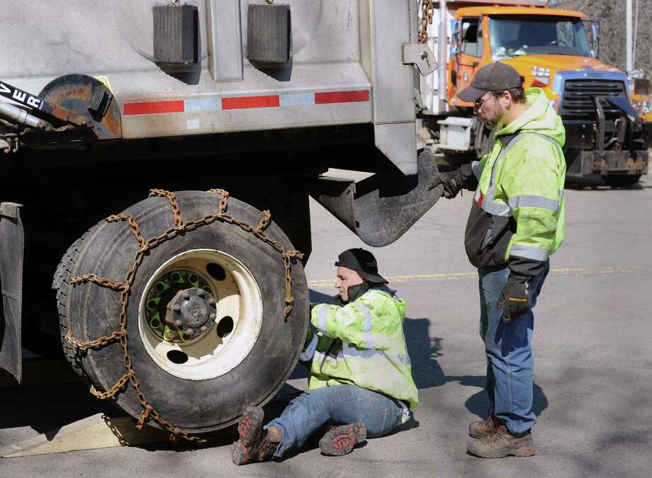 With help from Greenwich Department of Public Works co-worker, Dave Zboray, right, Dino Pereiro, bottom, places a chain on a truck tire as preparation for the forecasted nor'easter that is expected to hit early Wednesday morning, at the Greenwich Department of Public Works Indian Field Road site, Conn., Tuesday, March 6, 2018. Photo: Bob Luckey Jr. / Hearst Connecticut Media / Greenwich Time
