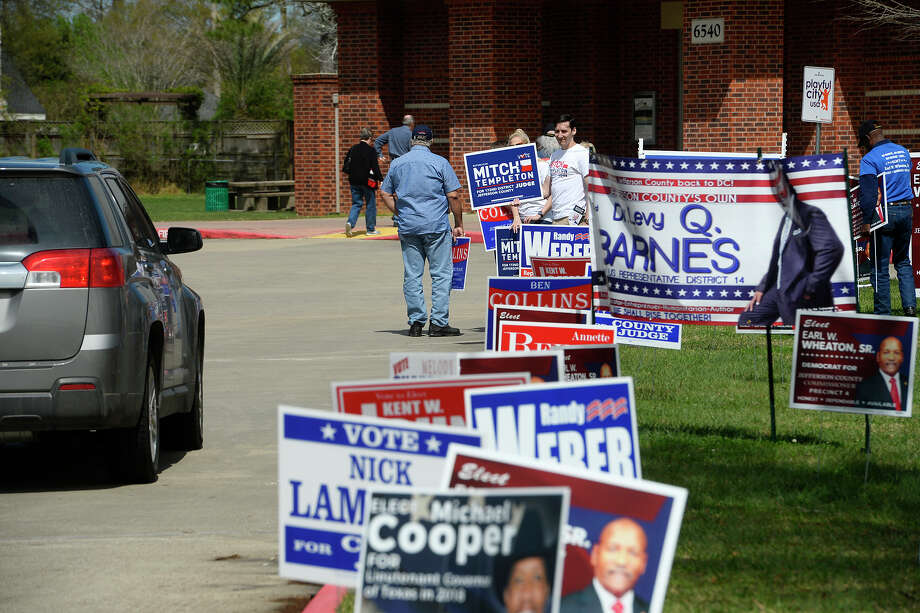 Campaign workers hold signs for their preferred candidates at the Rogers Park Community Center as voters show up for the primary election on Tuesday.  Photo taken Tuesday 3/6/18 Ryan Pelham/The Enterprise Photo: Ryan Pelham / ©2017 The Beaumont Enterprise/Ryan Pelham