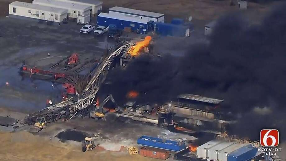 In this photo provided from a frame grab from Tulsa's KOTV/NewsOn6.com, fires burn at an eastern Oklahoma drilling rig near Quinton, Okla., Monday Jan. 22, 2018. Five people are missing after a fiery explosion ripped through a drilling rig, sending plumes of black smoke into the air and leaving a derrick crumpled on the ground, emergency officials said. (Christina Goodvoice, KOTV/NewsOn6.com via AP) Photo: Christina Goodvoice, Associated Press