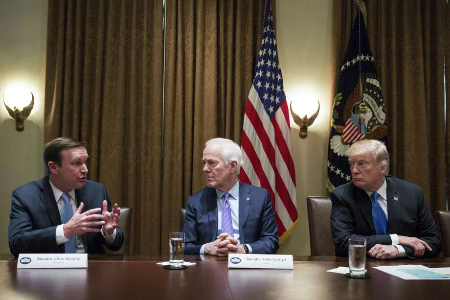 Senator Chris Murphy, a Democrat from Connecticut, from left, speaks as Senate Majority Whip John Cornyn, a Republican from Texas, and U.S. President Donald Trump listen during a meeting with bipartisan members of Congress to discuss school and community safety in the Cabinet Room of the White House in Washington, D.C., U.S. on Wednesday, Feb. 28, 2018. Trump has vowed to pass new laws designed to curb campus gun violence following the Feb. 14 shooting at a Parkland, Florida high school. Photo: Joshua Roberts / Bloomberg / © 2018 Bloomberg Finance LP