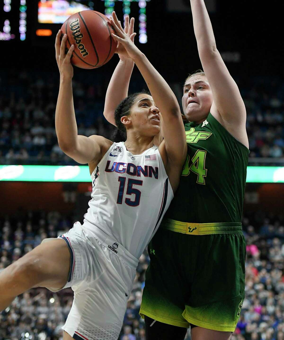 Connecticut's Gabby Williams, left, goes up to the basket as South Florida's Alyssa Rader, right, defends during the first half of an NCAA college basketball game in the American Athletic Conference tournament championship at Mohegan Sun Arena, Tuesday, March 6, 2018, in Uncasville, Conn.