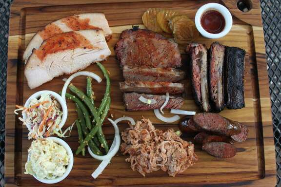 The Bushwood BBQ board consists of (clockwise from top left) smoked turkey, brisket, ribs, sausage, pulled pork, green beans with minced garlic, potato salad and cole slaw.
