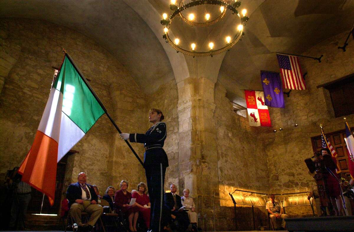 A member of the Lackland Air Force Base Honor Guard tips the Irish flag inside of the Alamo in 2001 in honor of Irish citizens that were killed during the battle of the Alamo. The annual memorial service there also honored Alamo war dead from other countries and numerous states accross America.