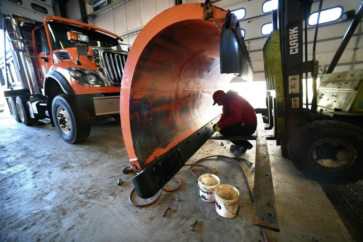 Nick Dadio installs bolts for a new cutting edge on a plow at the North Haven Department of Public Works on March 6, 2018 in preparation for heavy snow tomorrow.