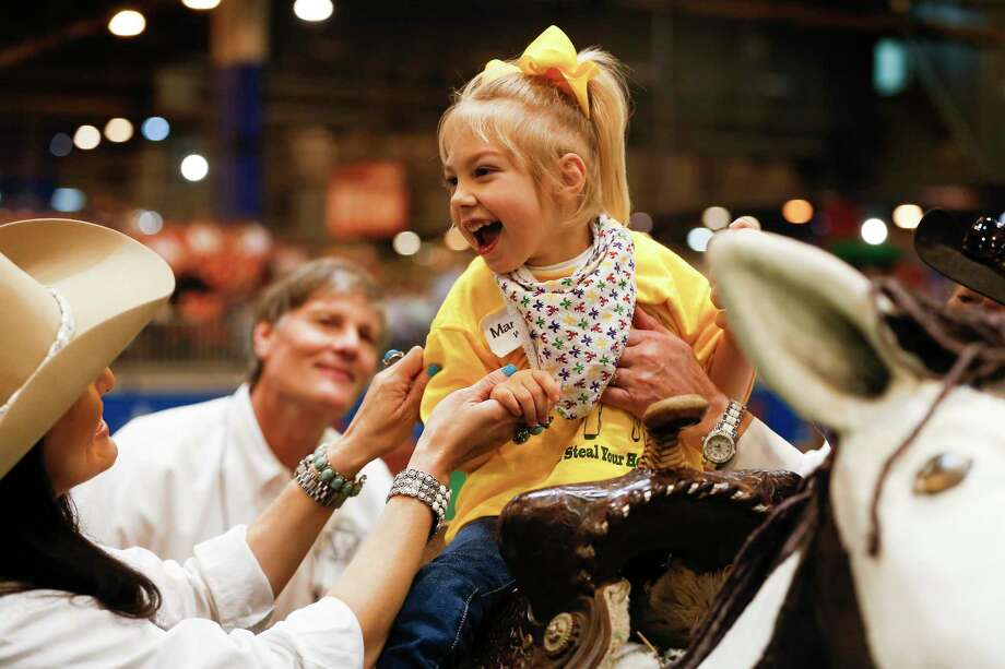 Mary Elizabeth Washington smiles a volunteer Amanda Moreno (left) as she rides a wooden horse during the Houston Livestock Show and Rodeo Lil' Rustlers event for kids with special needs Tuesday, March 6, 2018, in Houston. Photo: Steve Gonzales, Houston Chronicle / © 2018 Houston Chronicle