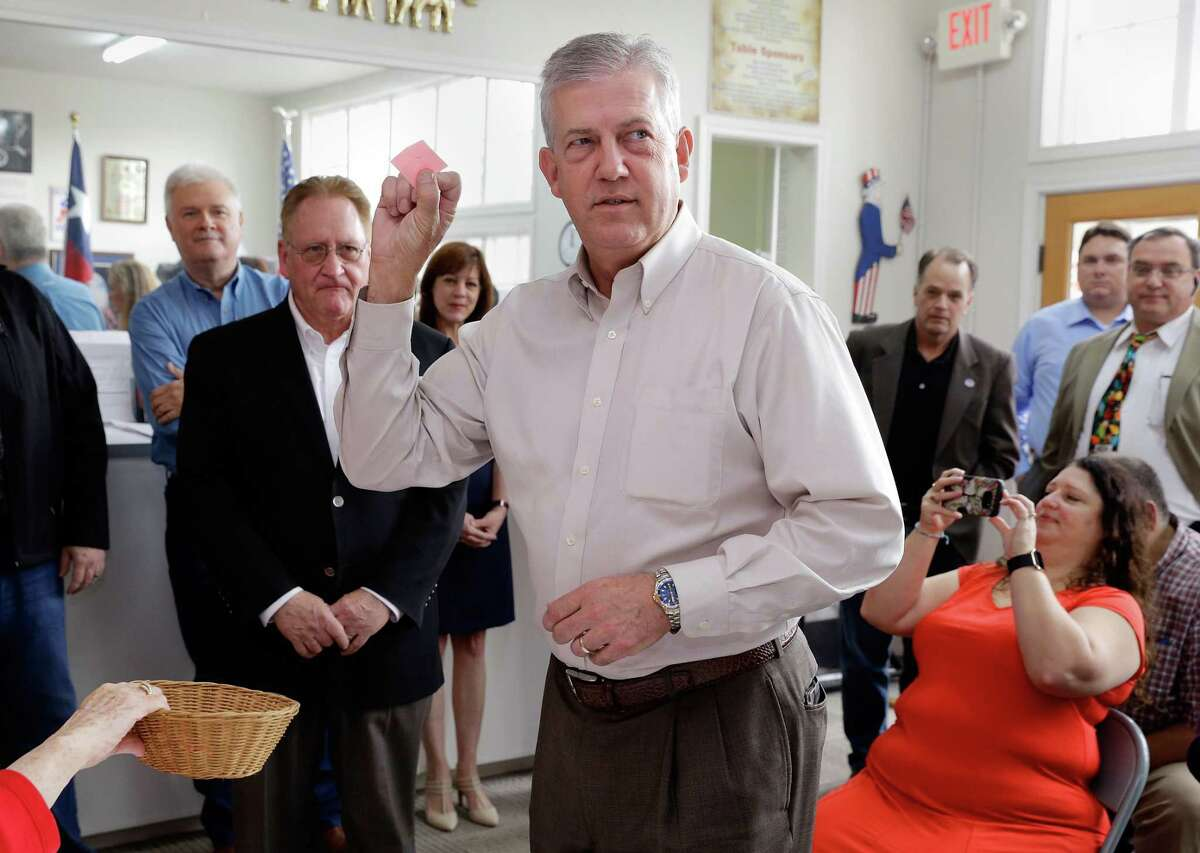 Judge Craig Doyal holds up his number one piece of paper as he draws for position on the ballot as his opponent Rep. Mark Keough (behind left) watches at the Montgomery County Republican Party office in Conroe, TX, Dec. 21, 2017. (Michael Wyke / For the Chronicle)