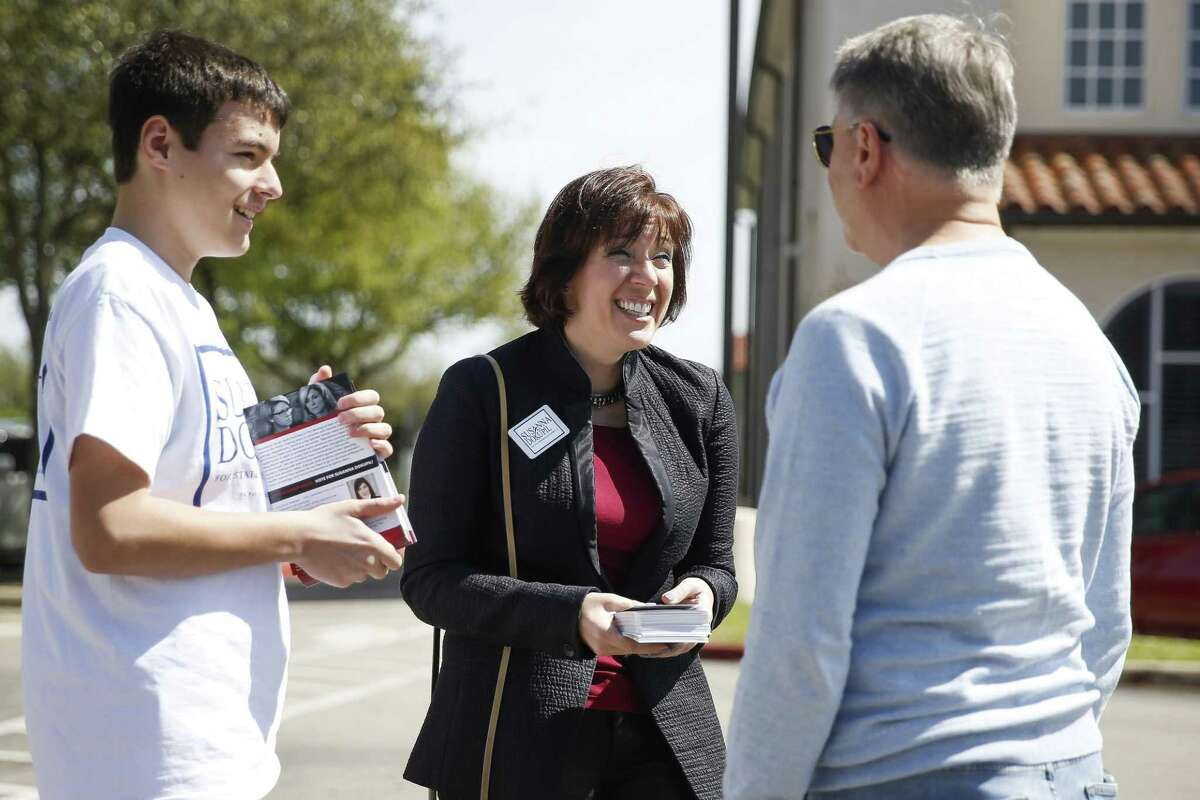 Republican candidate for House District 134 Susanna Dokupil, center, and her son, Benjamin Dokupil, 15, left, talk to Keith Lawyer, right, as she campaigns outside St Anne Catholic School Tuesday, March 6, 2018 in Houston. (Michael Ciaglo / Houston Chronicle)