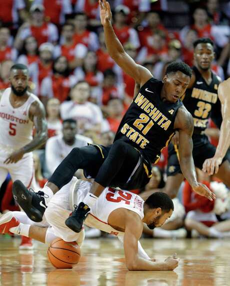 Wichita State forward Darral Willis Jr. (21) falls on Houston guard Galen Robinson Jr. (25) as they chase a loose ball during the second half of their game at H&PE Arena at Texas State University Saturday, Jan. 20, 2018, in Houston, TX. (Michael Wyke / For the  Chronicle) Photo: Michael Wyke, Freelance / © 2017 Houston Chronicle