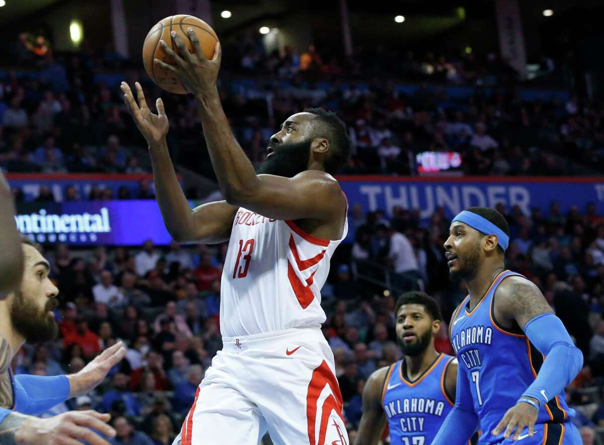 Houston Rockets guard James Harden (13) goes up for a shot between Oklahoma City Thunder center Steven Adams, left, forward Paul George (13) and forward Carmelo Anthony (7) in the first half of an NBA basketball game in Oklahoma City, Tuesday, March 6, 2018. (AP Photo/Sue Ogrocki)