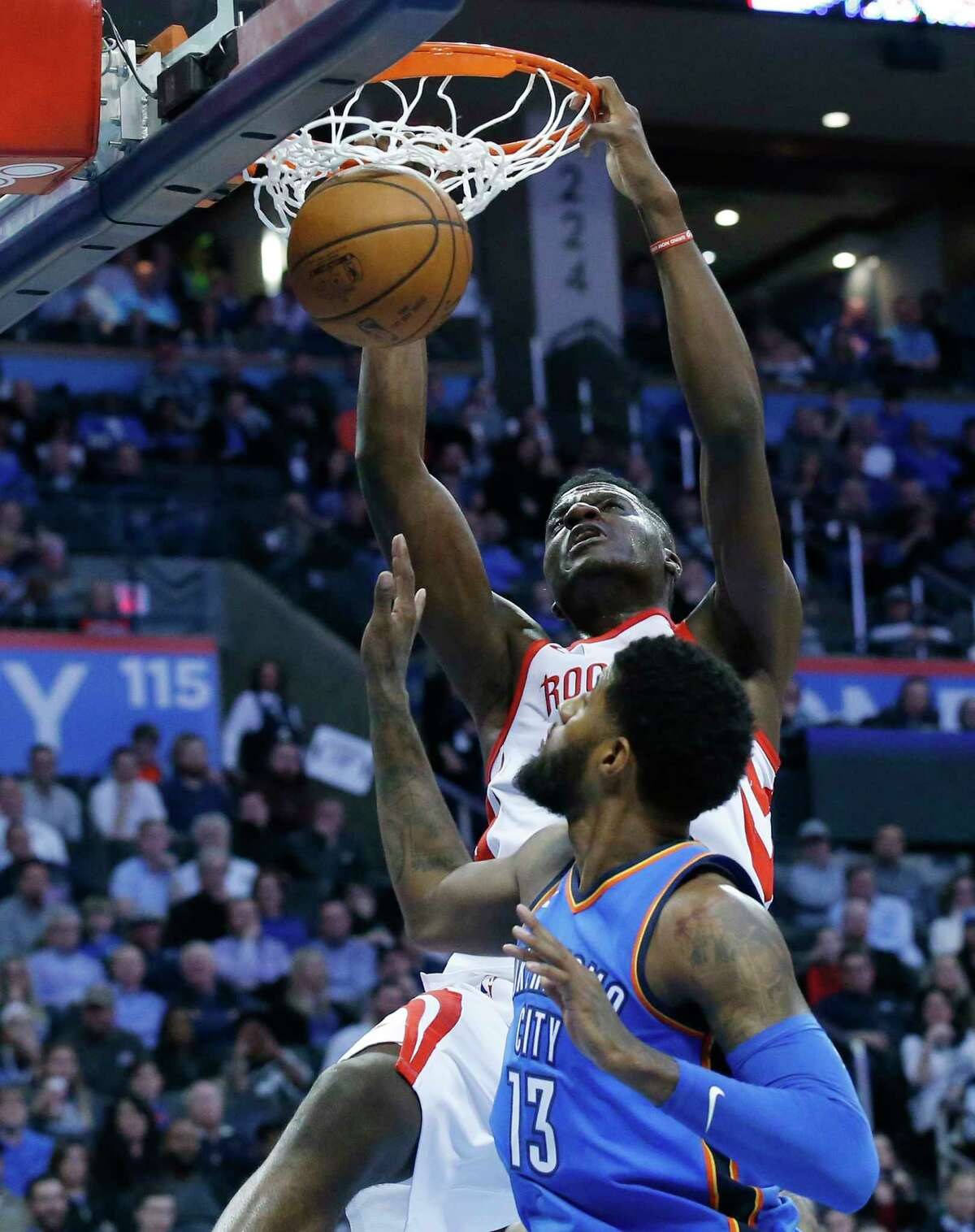 Houston Rockets center Clint Capela, rear, dunks over Oklahoma City Thunder forward Paul George (13) in the first half of an NBA basketball game in Oklahoma City, Tuesday, March 6, 2018. (AP Photo/Sue Ogrocki)