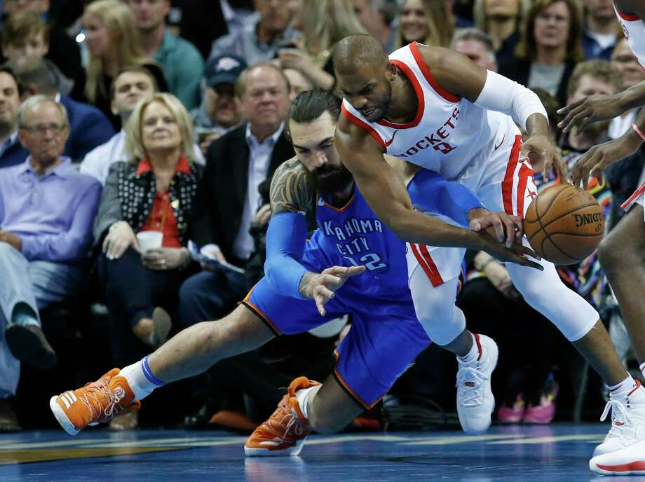 Oklahoma City Thunder center Steven Adams, left, reaches to in to knock the ball away from Houston Rockets guard Chris Paul, right, in the first half of an NBA basketball game in Oklahoma City, Tuesday, March 6, 2018. (AP Photo/Sue Ogrocki) Photo: Sue Ogrocki, Associated Press / AP2018